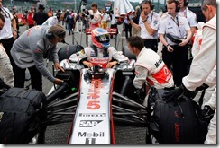 Jenson Button climbs in to his car on the grid
