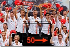 Jenson Button, Martin Whitmarsh and Sergio Perez lift thier 50th Anniversary Flat Caps during a team picture.