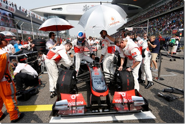 Jenson Button climbs from his car on the grid.