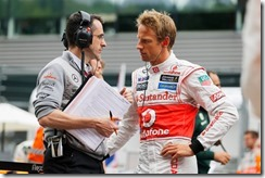 Jenson Button talks with engineer Dave Robson on the grid